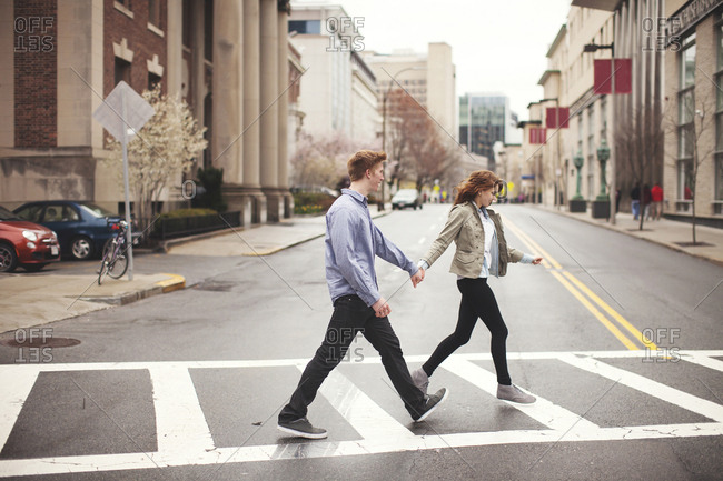 Caucasian couple holding hands crossing city intersection