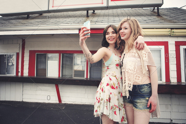 Caucasian friends taking selfie with cell phone