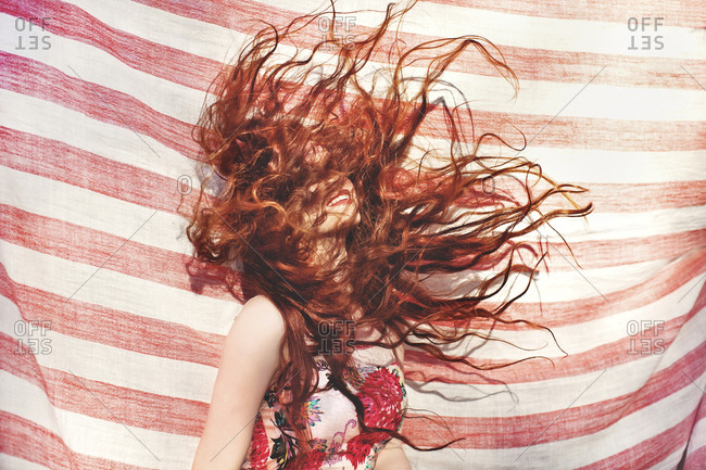 Hispanic woman tossing her hair near striped sheet