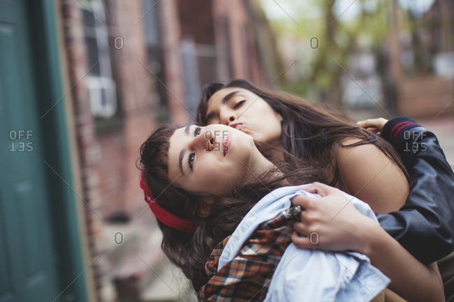 Friends kissing in city