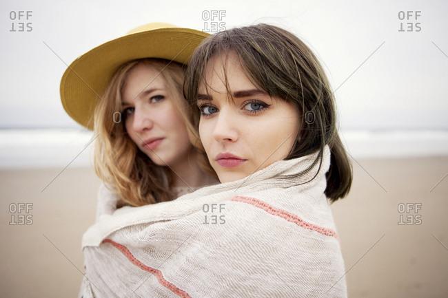 Caucasian friends wrapped in blanket on beach