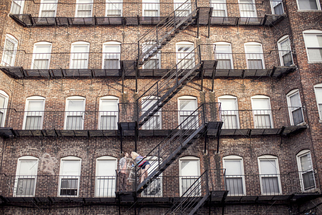 Caucasian couple standing on apartment fire escape