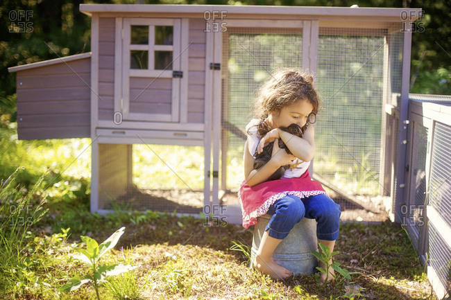 Girl hugging chicken in farm yard
