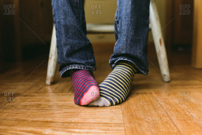 Childs feet with striped mismatched socks