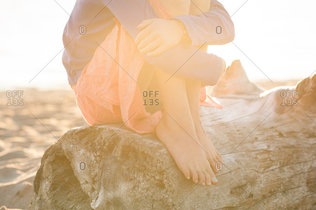 Barefoot girl sitting on log on a beach at sunset
