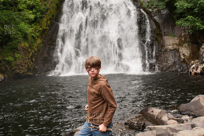 Boy standing by Young's River Falls in Oregon