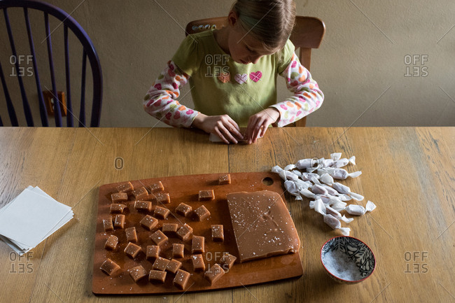Young girl wrapping salted caramels