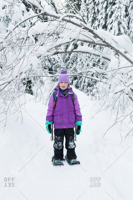 Girl in purple jacket walking in snow with snowshoes
