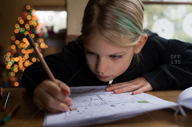 Little girl coloring picture with colored pencils
