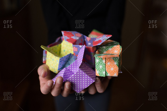 Child holding several colorful origami boxes
