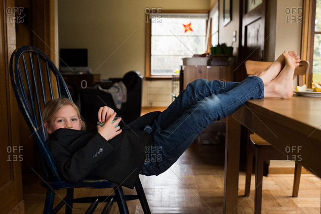 Girl eating snack with feet up on table