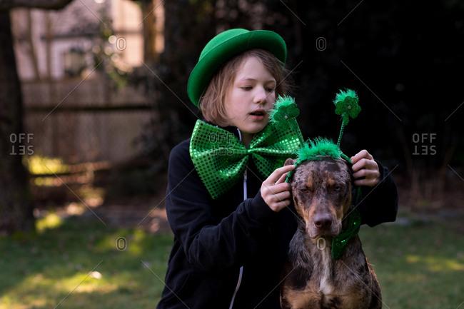 Child putting St. Patrick's day headband on her dog