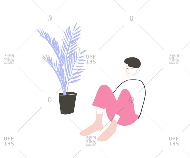 Person sitting on the floor next to a potted plant