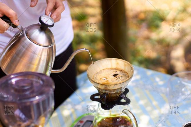 Pu'er, Yunnan, China - March 22, 2016: Woman brewing coffee outside
