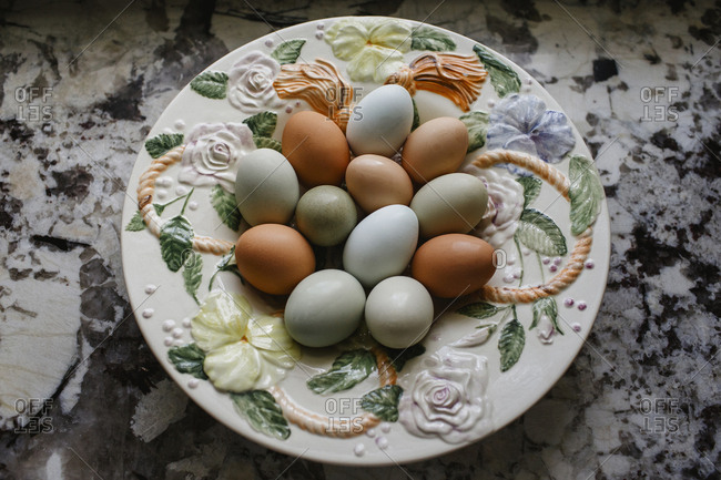 Fresh multi colored eggs in a ceramic floral bowl