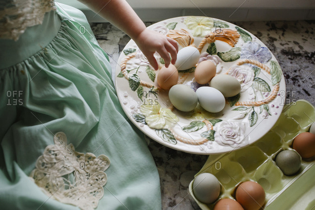 Girl's hand reaching for fresh egg to put in carton