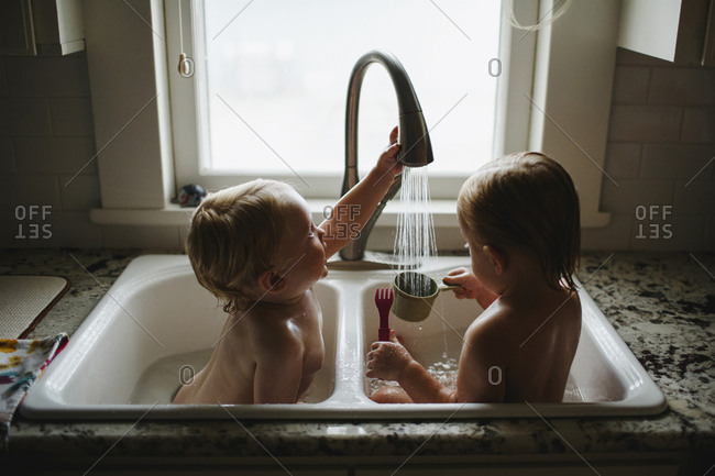 Brother and sister playing in the kitchen sink bath in front of a window