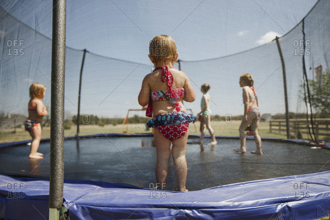Little girl standing on trampoline in bathing suit watching others play in the water