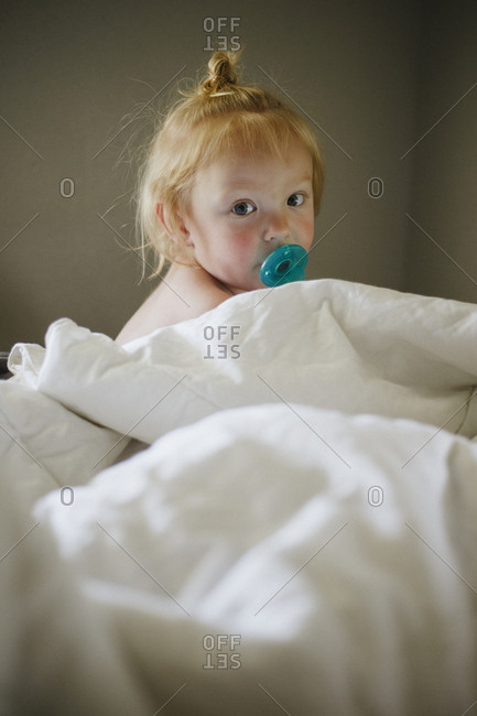 Little girl sitting on bed surrounded by blankets with pacifier