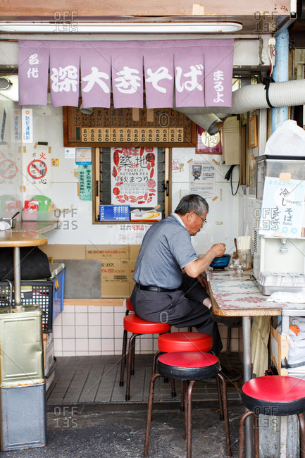 September 30, 2016 - Tokyo, Japan: Man eats soup in street food stall in the Tsukiji Fish Market