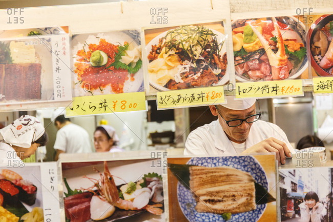 September 25, 2016 - Tokyo, Japan: A sushi chef in front of picture menus at the Tsujiki Fish Market