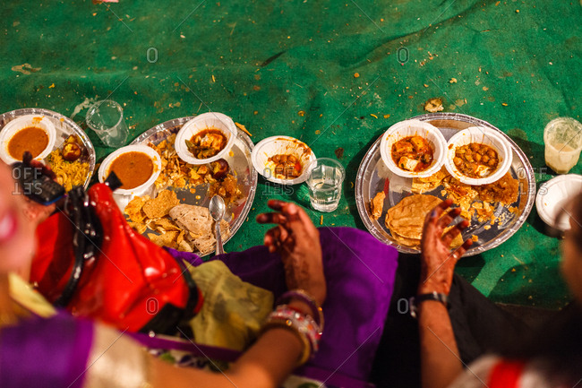 Woman eat traditional Indian food during a wedding reception in Pushkar, Rajasthan, India