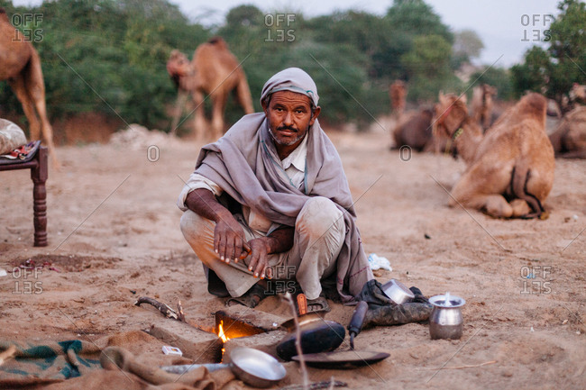November 14, 2015 - Pushkar, India: A man sits by a fire in the early morning on the dunes of the Pushkar Camel Fair