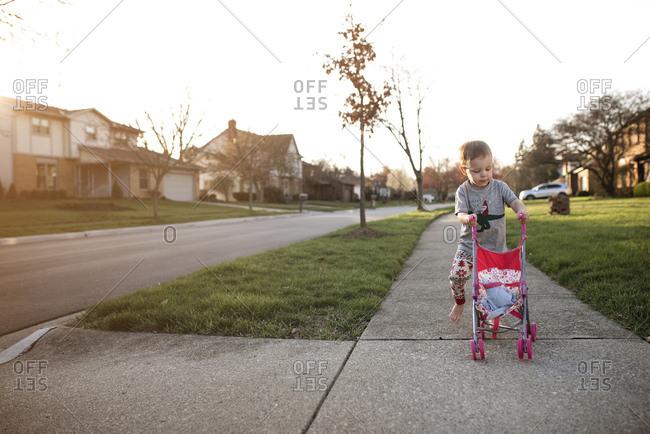 Child pushing stroller on sidewalk at dusk