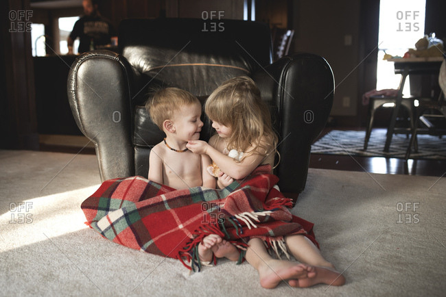 Two young siblings sitting together under blanket in living room