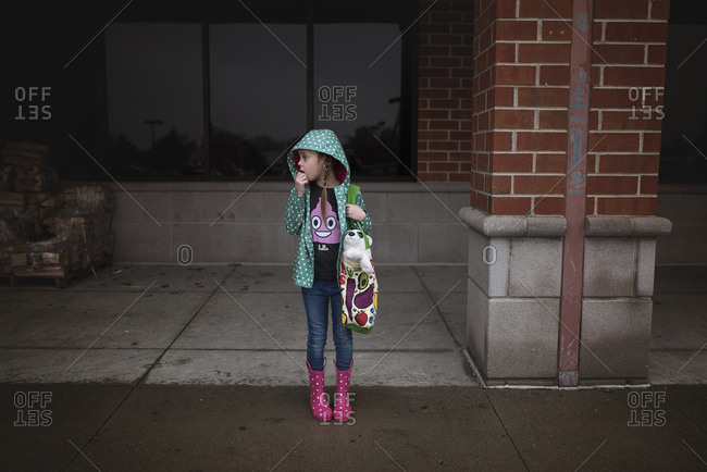 Young girl in rain boots and coat standing in front of building