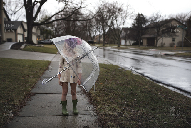 Young girl standing on sidewalk with umbrella