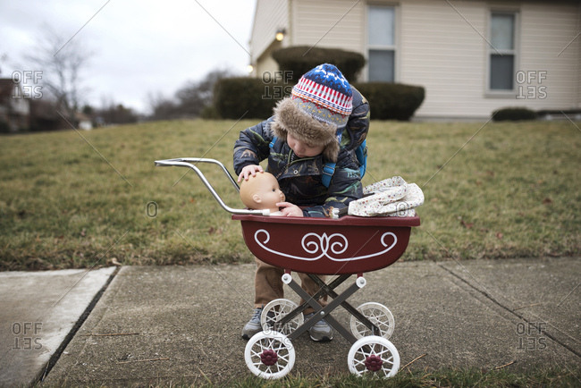 Boy putting doll in baby carriage