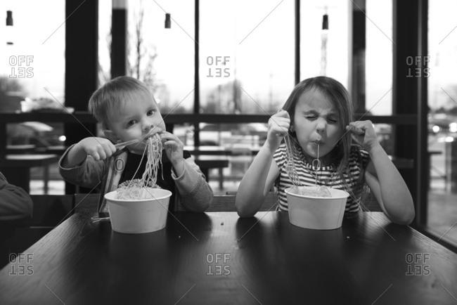 Two young children eating ramen in restaurant
