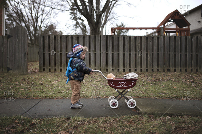Boy pushing doll in baby carriage