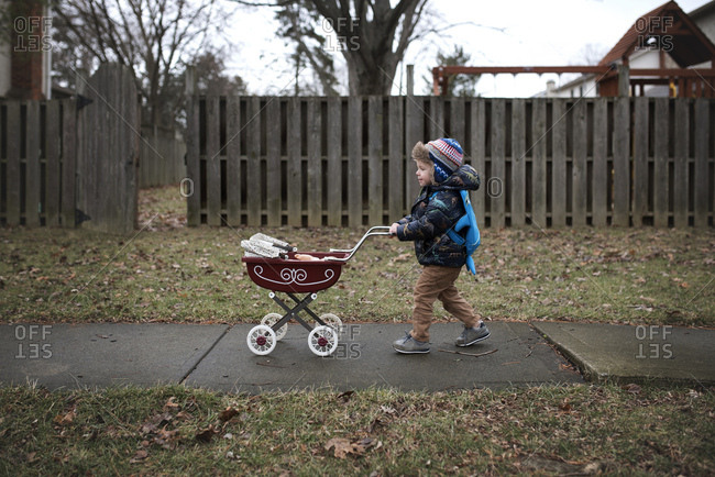 Little boy pushing doll in carriage on sidewalk