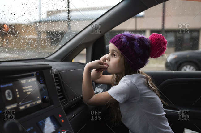 Girl in hat waiting in front seat of car