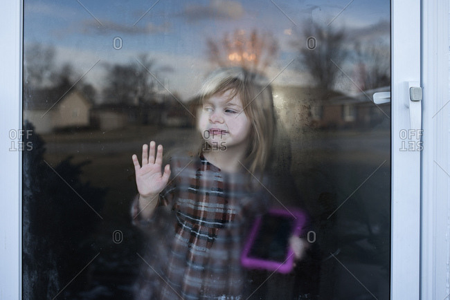 Girl pressing her face against foggy window