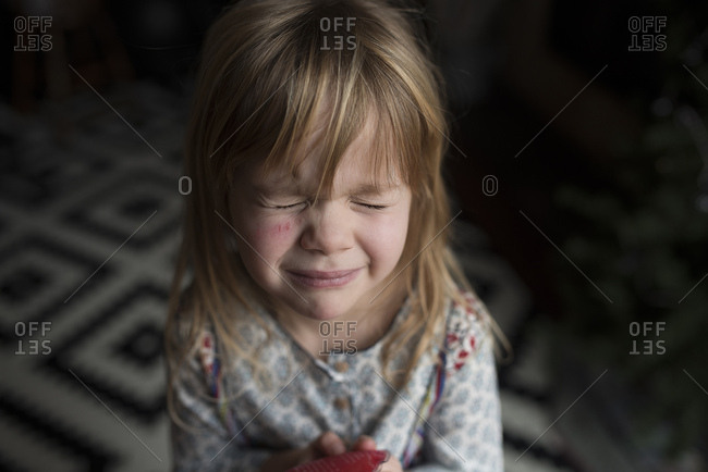 Young girl with a scratch on her face closes her eyes