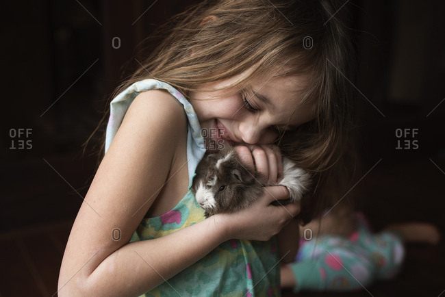 Young girl hugging her guinea pig