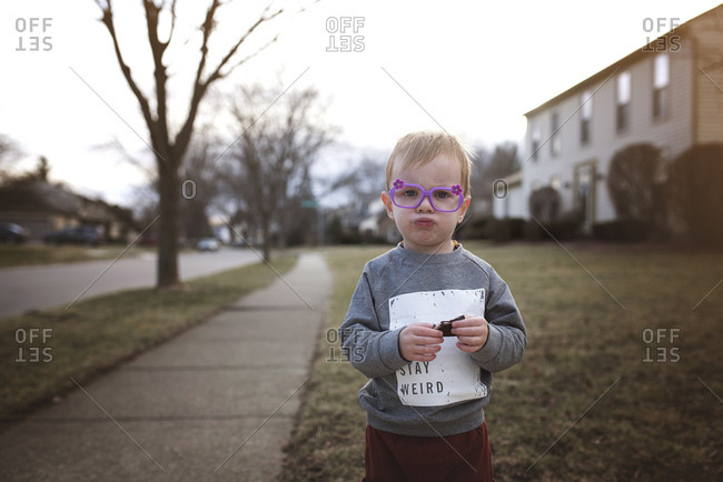 Boy in purple flowered glasses makes a funny face