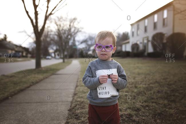 Boy in purple flowered glasses eating cookie on sidewalk