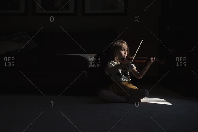 Sunlight shining on young girl playing violin