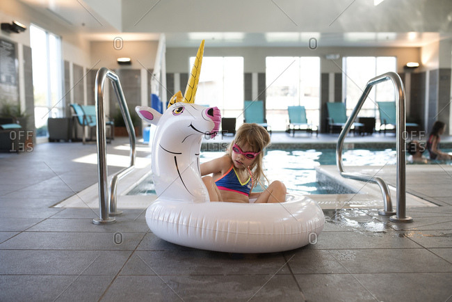 Young girl playing on unicorn float at pool