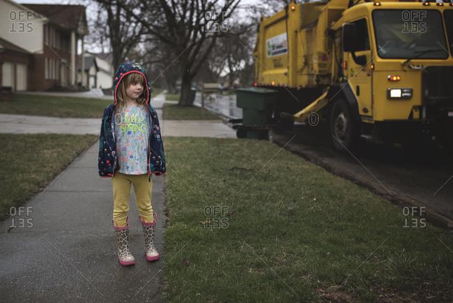 Girl standing on sidewalk near garbage truck
