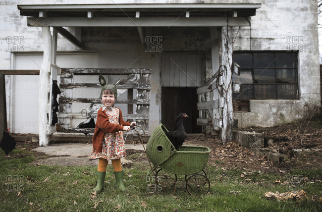 Child with chicken in baby carriage