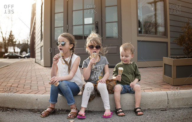 Three young children sitting on curb eating ice cream