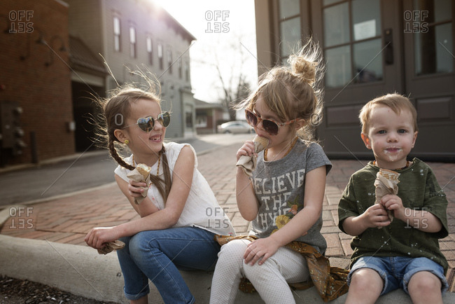 Happy young children seated on curb and enjoying ice cream at dusk