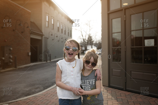 Smiling young sisters in sunglasses on street corner at dusk