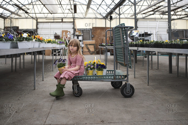 Girl holding pot of flowers in garden center
