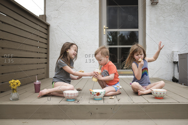 Three young children eating lunch together outdoors